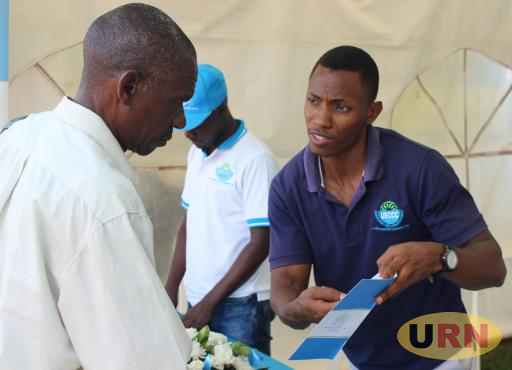 Henry Jumba explains how UECCC works to a visitor at the Energy Week exhibition in Kampala