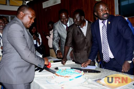 David Lukyamuzi Kalwanga, the Busujju County Member of Parliament (left) joined by a section of NRM MPs to cut cake at parliament.