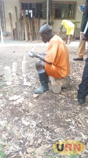 An inmate at Kiburara prison works on a wooden sculpture