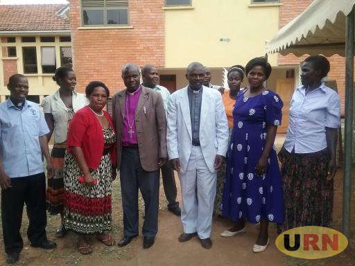 Bishop Samuel Gidudu  wearing a purple shirt  with some of the reverands and their spouses