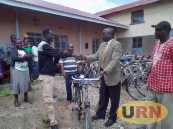 CAO Moroto, Martin Jaachan Gwokto hands over the bicycle to Jeremy Lomonyang, community animal health worker in Nadunget sub county.
