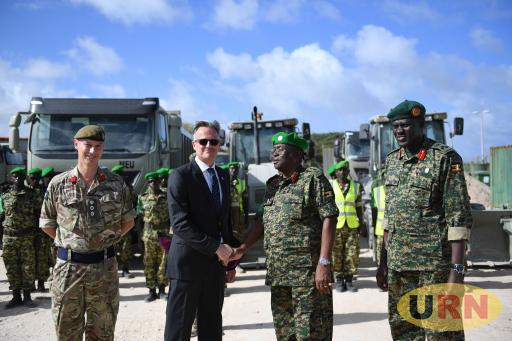 David Concar, the UK Ambassador to Somalia chats with overall AMISOM commander Lt. Gen. Jim Beesigye Owoyesigire and commander of Ugandan AMISOM sector one forces, Brig Gen Paul Lokech after handover of the equipment