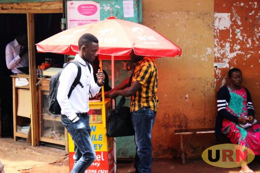 A man walks past a Mobile Money agent in Wandegeya, Kampala.