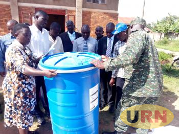 Luweero district officials looking at air tight super grain plastic bag which is modern form of storage. It can store 450 kilograms of maize grain