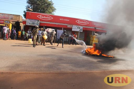 Police put off fire from the tires that were lit by people power sympathizers in the middle of Jinja-Iganga high way on Friday.