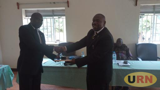 Ismail Ochengel the interdicted CAO (r) handing over files to the new CAO Donath Eswilu at the district board room as RDC Nahori Oyaa looks on today