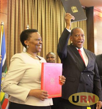 Energy Minister, Engineer Irene Muloni(L) exchanging signed agreements with Tanzania's former  Constitutional and Legals Affairs Minsiter , Professor Palamagambi Kabudi